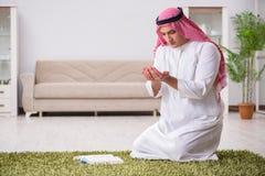 L'homme arabe priant à la maison photo stock