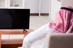 L'homme arabe regardant la TV à la maison photo stock