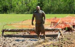 L'homme asiatique barbu regarde fixement vers le bas parcours du combattant pendant la course annuelle de boue Photographie stock libre de droits