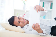 L'homme asiatique écoutent chanson sur le sofa Photo stock
