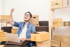 L'homme asiatique de jeune succès heureux avec sa main se soulèvent  image stock