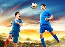 L'homme asiatique de joueur de football deux sautent à l'air et au duel dirigeant la boule images stock