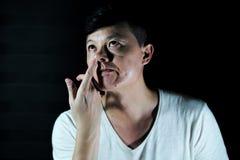 L'homme asiatique de portrait essaye de dégager la morve de son nez images stock