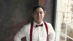 L'homme asiatique de Portret dans des bretelles regarde l'appareil-photo et sourit clips vidéos