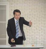 L'homme asiatique de sourire dans le costume noir avec le marteau en bois attendent à disposition des personnes offrant le concep photo libre de droits