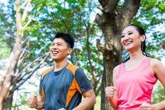 L'homme asiatique et la femme chinois pulsant dans la ville se garent Photos stock