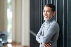 L'homme asiatique mûr attirant de portrait s'est retiré avec la barbe courte élégante souriant au café extérieur photographie stock