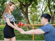 L'homme asiatique se met à genoux vers le bas donnant à son amie par groupe de roses Images stock
