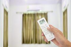 L'homme Asie de main tient un à télécommande du climatiseur 25 Photo stock