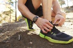 L'homme attache la chaussure de sports avant la course dans une forêt, fin vers le haut de détail Photos libres de droits