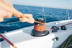 L'homme attache la corde nautique sur le treuil sur le bateau Images libres de droits