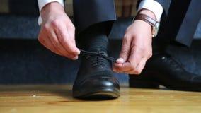 L'homme attache les dentelles sur les chaussures noires Plan rapproché des mains et des chaussures clips vidéos