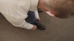L'homme attache ses chaussures noires En gros plan, Bridegirl lie ses chaussures en noir et blanc un futur mari serre pour a clips vidéos