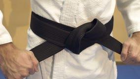 L'homme attache une ceinture noire sur un kimono blanc clips vidéos