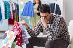 L'homme attendant son épouse pendant les achats de Noël photographie stock libre de droits