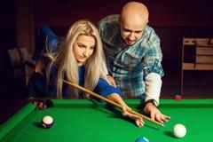 L'homme attirant enseigne la femme commence le jeu sur la table de billard Photos stock