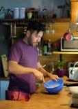 L'homme attirant fait cuire sur la cuisine à la maison, intérieur en bois confortable photographie stock