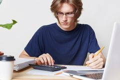 L'homme attirant fait face à la crise financière, étudie l'avis de la banque, calcule des chiffres L'étudiant masculin étudie des Photos stock