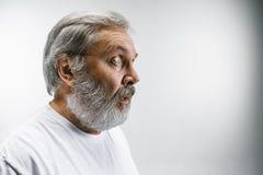 L'homme attirant supérieur semblant étonné d'isolement sur le blanc Photo libre de droits