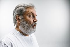 L'homme attirant supérieur semblant étonné d'isolement sur le blanc Photo stock