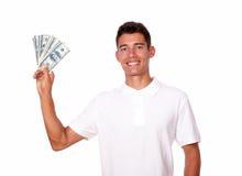 L'homme attirant tient l'argent dans une main. Photo stock