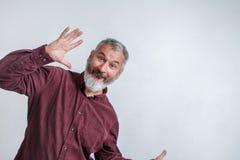 L'homme aux cheveux gris adulte avec une barbe dans une chemise rouge sourit et ondule ses bras contre un mur blanc image libre de droits
