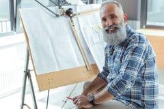 L'homme aux cheveux gris plus âgé délicieux apprécie son travail Image libre de droits