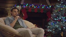 L'homme aux cheveux longs boit du vin dans la nuit de Noël par l'arbre décoré banque de vidéos