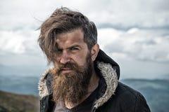 L'homme avec l'aspect barbu brutal, homme non rasé brutal semble désordonné L'homme avec la longues barbe et moustache utilise la photo stock