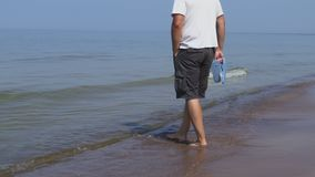 L'homme avec des bascules électroniques dans des ses bras marche le long de la mer clips vidéos
