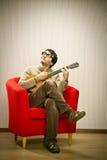 L'homme avec des verres jouent l'ukulélé sur la chaise rouge Images libres de droits