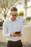 L'homme avec des verres parlent du téléphone portable dans des mains Photo libre de droits