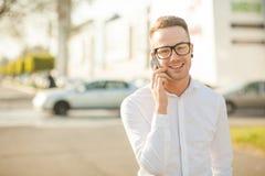 L'homme avec des verres parlent du téléphone portable dans des mains Photos stock