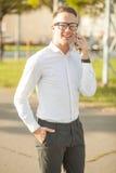 L'homme avec des verres parlent du téléphone portable dans des mains Photo stock