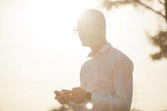 L'homme avec des verres parlent du téléphone portable dans des mains Images libres de droits