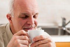 L'homme avec des yeux clôturent tenir le café jusqu'à son nez Photo stock