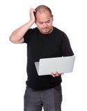 L'homme avec l'ordinateur portable et rayent sa tête photos stock