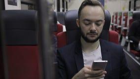 L'homme avec la barbe dans la chaise d'autobus lit de l'écran de smartphone banque de vidéos