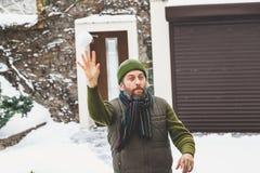 L'homme avec la barbe dans ses jets de chapeau lance des boules de neige dans la cour Image libre de droits
