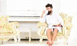 L'homme avec la barbe et la moustache apprécie le matin tout en se reposant sur le fauteuil de luxe Concept de loisirs d'élite Ho Photographie stock