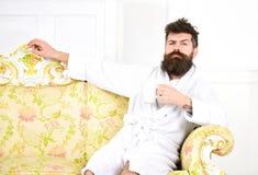 L'homme avec la barbe et la moustache apprécie le matin tout en se reposant sur le sofa de luxe Concept de loisirs d'élite Homme  Photos libres de droits