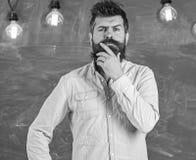 L'homme avec la barbe et la moustache sur le visage réfléchi se tiennent devant le tableau Concept intellectuel de tâche Pensée d image libre de droits