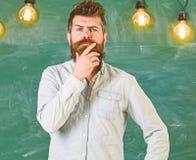 L'homme avec la barbe et la moustache sur le visage réfléchi se tiennent devant le tableau Concept intellectuel de tâche Pensée d photos stock