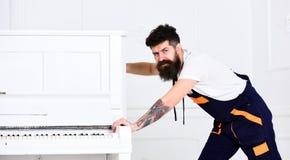 L'homme avec la barbe et la moustache, travailleur dans des combinaisons pousse le piano, fond blanc Le messager livre des meuble photo libre de droits