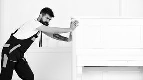 L'homme avec la barbe et la moustache, travailleur dans des combinaisons pousse le piano, fond blanc Le messager livre des meuble photos libres de droits