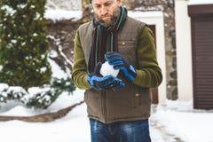 L'homme avec la barbe fait la boule de neige dans la cour Photos stock