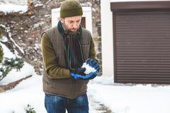 L'homme avec la barbe fait la boule de neige dans la cour Images stock