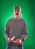 L'homme avec la barbe grise dans un chef de costume et de chapeau de marin tenant le couteau et le légume Image libre de droits