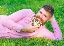 L'homme avec la barbe sur le visage de sourire apprécient la nature Concept de masculinité Homme barbu avec des fleurs de marguer photos libres de droits