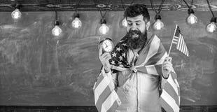 L'homme avec la barbe sur le visage gai tient le drapeau des Etats-Unis et l'horloge, tableau sur le fond, l'espace de copie ?duc images libres de droits